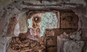 Pipe behinde a wall breakthrough in the Whitney-Houston-House, Beelitz