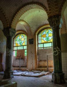 A ruined bathroom with colored windows in Beelitz Heilstätten